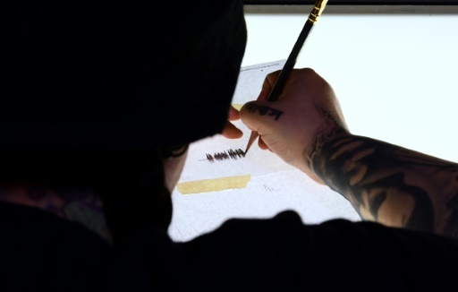 """La tatoueuse Tiffany Garcia réalise le """"Soundwave Tattoo"""" d'Hanna Washlake en Californie, à Torrance le 12 avril 2018 © FREDERIC J. BROWN AFP"""