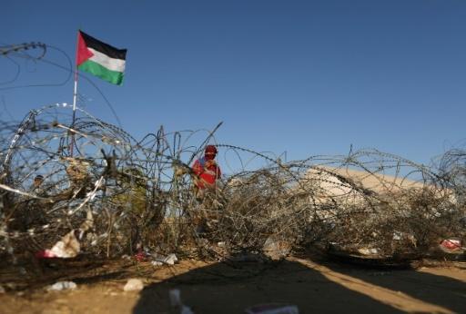 """Un Palestinien se tient derrière des barbelés dans un des camps de tentes montés le long de la frontière entre la bande de Gaza et Israël à l'occasion de la """"Marche du retour"""", le 22 avril 2018 près de Khan Younès  © MAHMUD HAMS AFP"""