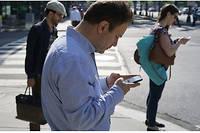 Des piétons absorbés par leur smartphone et livrés aux risques de la circulation.  ©MANDEL NGAN