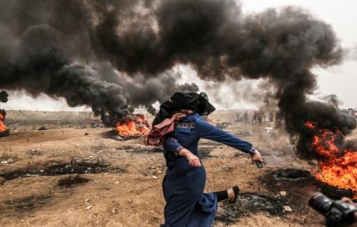Une Palestinienne lance des pierres en direction des forces israéliennes lors d'une mobilisation le long de la frontière de la bande de Gaza, le 4 mai 2018 © MAHMUD HAMS AFP