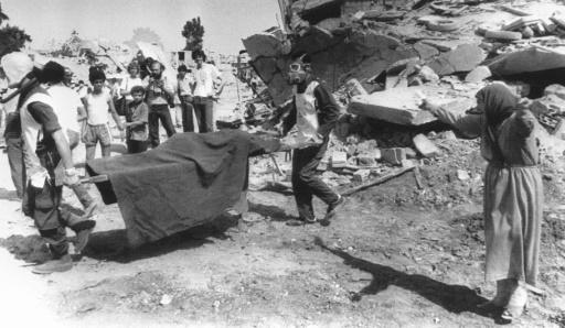 Une femme pleure alors que des travailleurs humanitaires transportent le corps d'un de ses proches, dans le camp de réfugiés palestiniens de Sabra, dans l'est de Beyrouth, le 19 septembre 1982 © STF AFP/Archives