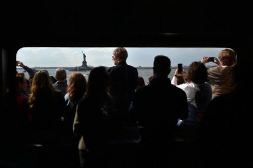 Des personnes sur le pont d'un ferry photographient la Statue de la Liberté, le 28 avril 2018 à New York © HECTOR RETAMAL AFP