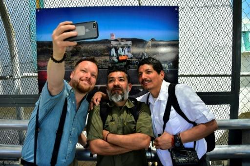 Des photographes de l'AFP (g-d) Jim Watson, Guillermo Arias et Yuri Cortez font un selfie lors de l'inauguration de l'exposition sur la vie à la frontière entre le Mexique et les Etats-Unis à Ciudad Juarez, le 4 mai 2018 © Pedro PARDO AFP