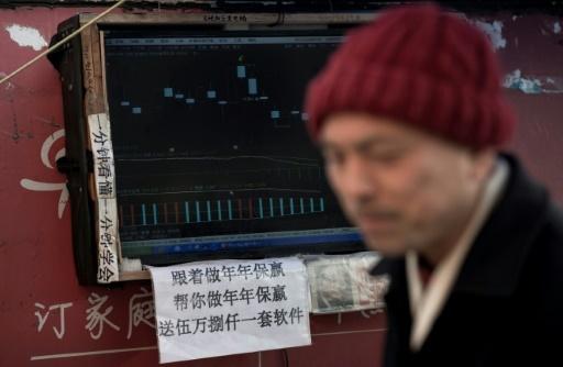 Un boursicoteur explique la volatilité des cours devant son ordinateur à Shanghai, le 25 mars 2018 © Johannes EISELE AFP