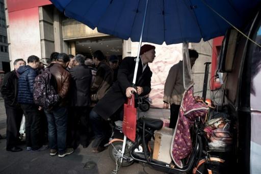Chaque week-end, ce sont désormais plusieurs dizaines de boursicoteurs qui se retrouvent au même coin de rue à Shanghai © Johannes EISELE AFP