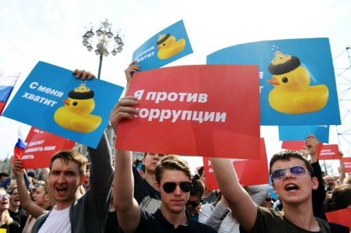 """Des manifestants anti-Poutine randissent des affiches où il est écrit """"ça suffit"""" et """"Je suis contre la corruption"""" à MOscou, le 5 mai 2018 © Kirill KUDRYAVTSEV AFP"""