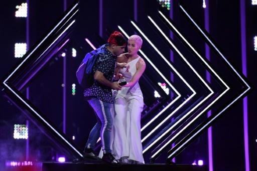 Un spectateur s'empare du micro de la Britannique Susanna Marie Cork alias SuRie avant d'être interpellé pendant la finale de la 63e édition du concours de l'Eurovision, à Lisbonne le 12 mai 2018 © Francisco LEONG AFP