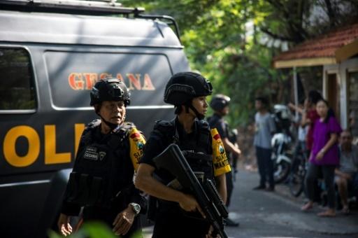 Des policiers patrouillent devant une église après les attentats à la bombe qui ont fait au moins 111 morts à Surabaya, en Indonésie, le 13 mai 2018 © JUNI KRISWANTO AFP