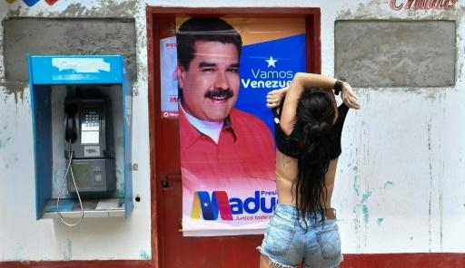 Une femme soulève son tee-shirt devant une affiche de campagne du président vénézuélien, Nicolas Maduro, dans l'Etat de Choroni-Aragua, au Vénézuela, le 12 mai 2018 © JUAN BARRETO AFP
