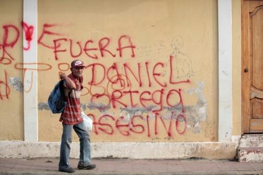 """Un homme âgé passe devant un slogan peint sur un mur à Masaya au Nicaragua, réclamant: """"Dehors l'assassin Daniel Ortega"""", le 12 mai 2018 © DIANA ULLOA AFP"""