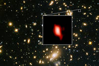 La lointaine galaxie MACS 1149-JD1 observée par ALMA, resituée par rapport à l'amas de galaxies MACS j1149.5+223 qui a servi de lentille gravitationnelle pour sa détection.