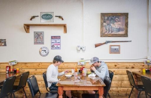 """Des clients sont attablés au restaurant """"Shooters Grill"""" à Rifle dans le Colorado (ouest des Etats-Unis) qui célèbre le deuxième amendement qui garantit le droit de porter des armes © EMILY KASK AFP"""