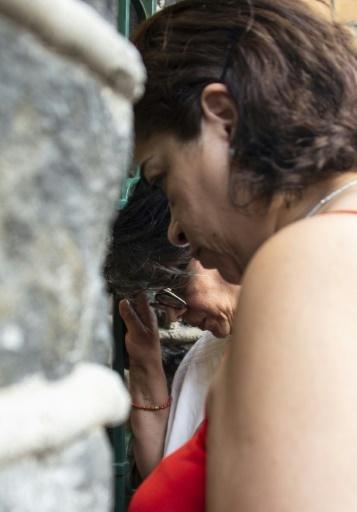 Des proches d'un membre de l'équipage de l'avion qui s'est écrasé à Cuba se recueillent au siège de la compagnie aérienne Global Air à Mexico, le 18 mai 2018 © PEDRO PARDO AFP
