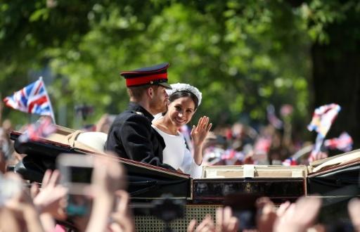 Le prince Harry et son épouse Meghan Markle saluent la foule depuis leur calèche après leur mariage, le 19 mai 2018 à Windsor © Daniel LEAL-OLIVAS AFP