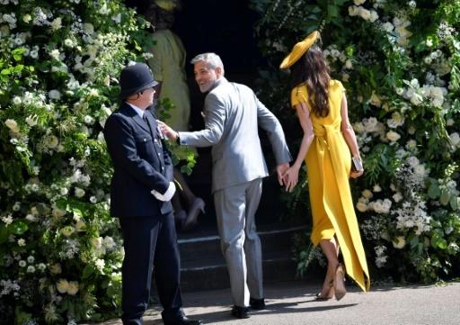 L'acteur George Clooney et son épouse Amal saluent un policier en arrivant au mariage royal à Windsor, le 19 mai 2018 © TOBY MELVILLE POOL/AFP