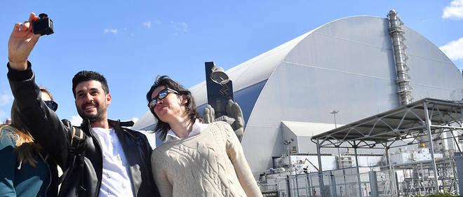 Des touristes à Tchernobyl devant le nouveau sarcophage de confinement du réacteur n°4. La catastrophe de 1986 est un « cas d'école » selon Daniel Heuer pour qui, dans la centrale, « tout semble avoir été fait pour qu'elle finisse par exploser ».