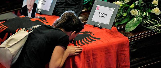 Des proches s'inclinent devant les cercueils des victimes.Ici les deux victimes albanaises recouvert du drapeau de leur pays. Un moment dédié leur a été copnsacré pendant la cérémonie des funérailles, déclenchant les applaudissements de l'assistance.