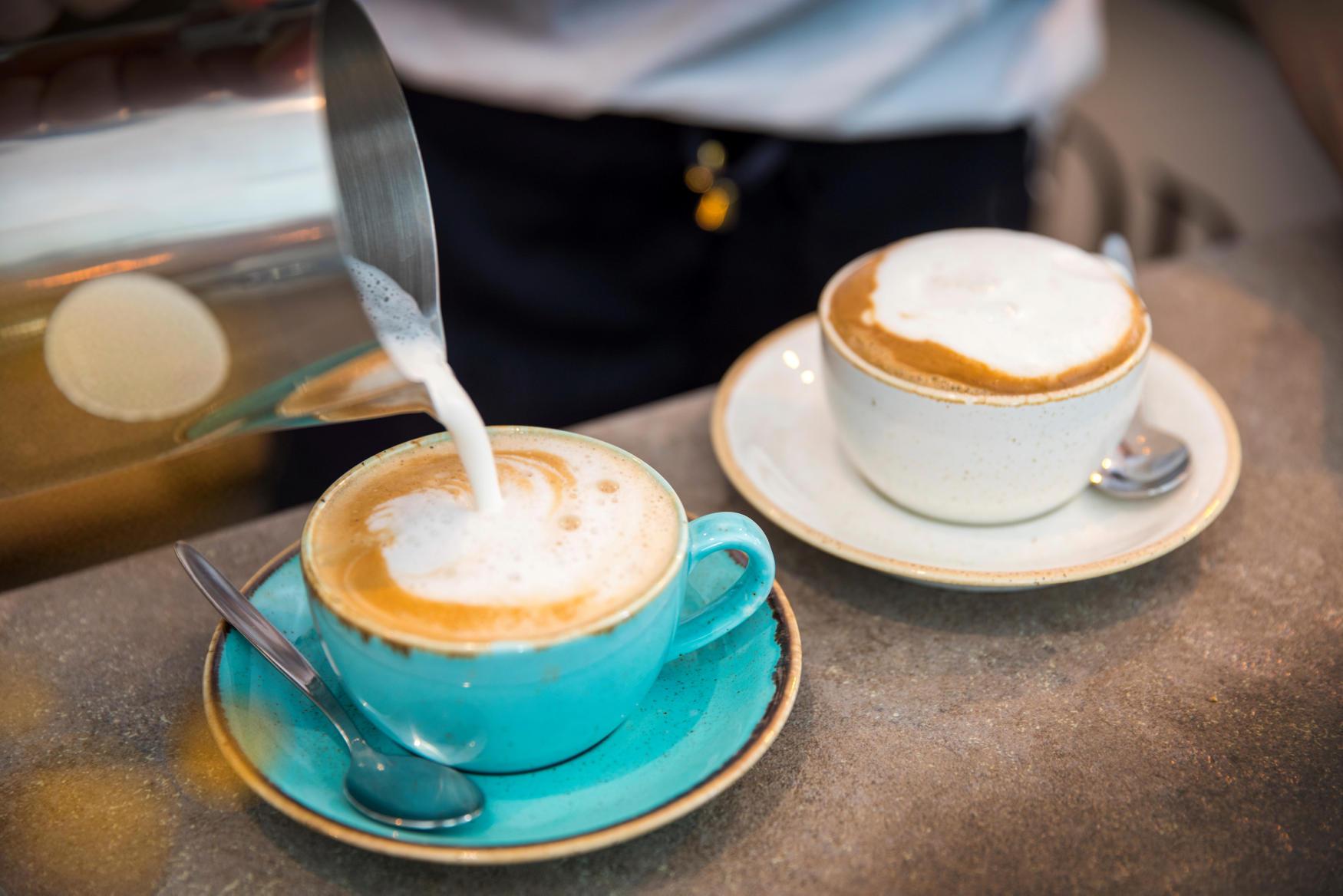 Barista pouring frothy milk into coffee cup, close-up