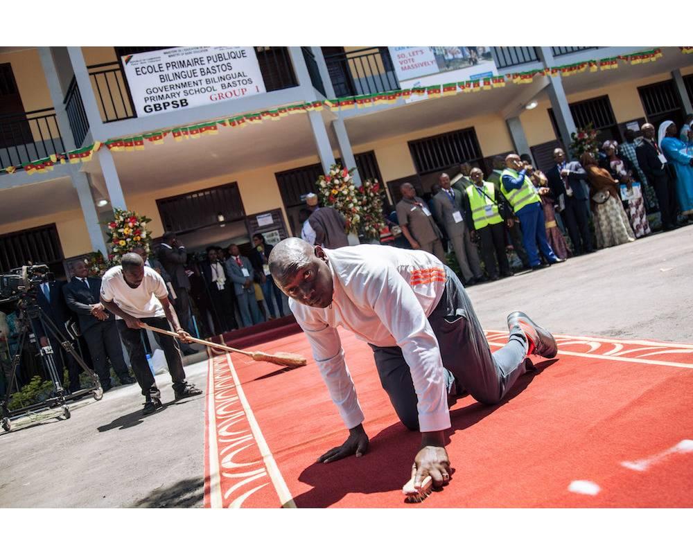 Quand le tapis rouge du président est nettoyé avant son arrivée... Entre pompe officielle et réalités du terrain. © AFP/ALEXIS HUGUET
