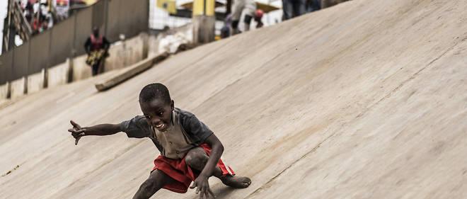 Un jeune garçon glisse le long des murs de confinement d'une voie de chemin de fer du district de Viana à Luanda, où vivent plus de 5 millions de personnes dans des quartiers informels.