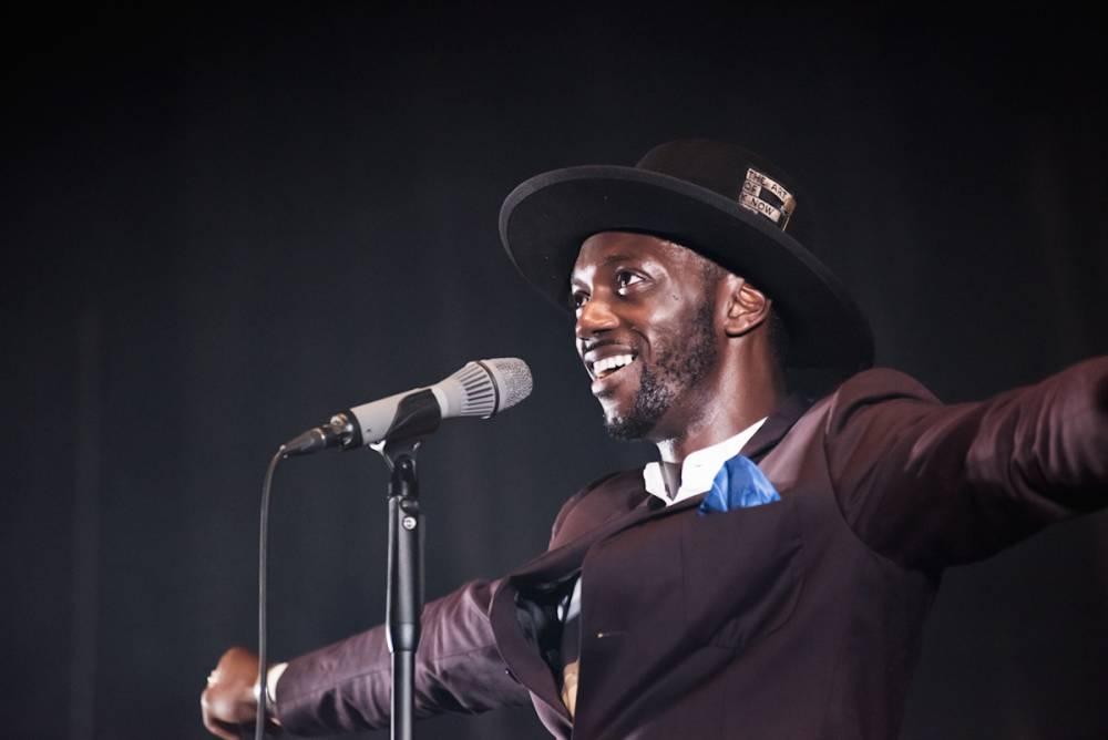 Costume chic, cape de plumes bleues sur les épaules, le chanteur et compositeur Belgo-congolais Baloji est, à l'image de sa musique, un doux mélange d'influences.  ©  Jean de Pena