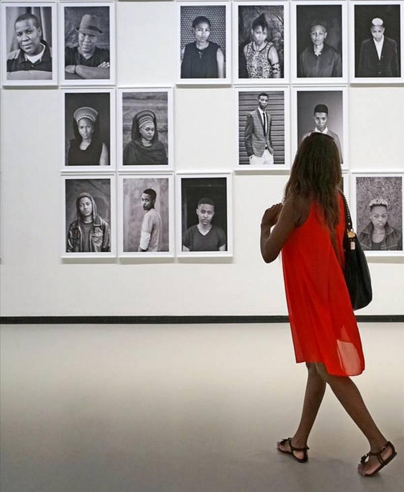 Visiteuse de l'exposition « Art/Afrique » devant des portraits de Zanele Muholi, Fondation Louis Vuitton, juillet 2017, Paris. ©  Jean‑Pierre Dalbéra