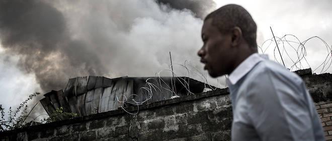 13 décembre 2018, l'entrepôt de la Ceni est en feu alors qu'un Kinois passe à côté.