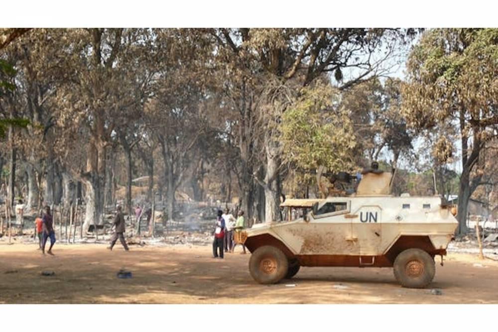 Des déplacés revenant dans les ruines du camp d'Alindao, le 17 novembre, sous la protection d'un véhicule blindé burundais de la Minusca.  ©  Benoît Lallau/DR, Author provided