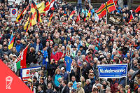Supporters of the Pegida (Patriotic Europeans Against the Islamisation of the Occident) take part in a protest against German Chancellor Angela Merkel and her policy on October 3, 2016 in Dresden, eastern Germany, where the Chancellor and representatives of the country's constitutional body had come together before to celebrate the Day of German Unity. - Dresden, a Baroque city in Germany's ex-communist east, is the birthplace of the anti-immigration PEGIDA street movement. (Photo by Odd ANDERSEN / AFP) ©ODD ANDERSEN