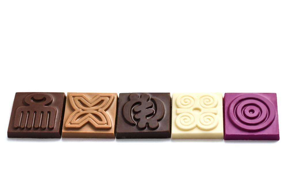 Un échantillon, des carrés de chocolats issus des barres Adinkra gravées de symboles visuels qui font référence à l'ethnie Ashanti du Ghana.  ©  DR