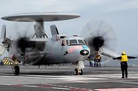Un avion-radar Hawkeye déploie ses ailes sur le pont du porte-avions  Charles de Gaulle , fin janvier 2019 en Méditerranée.