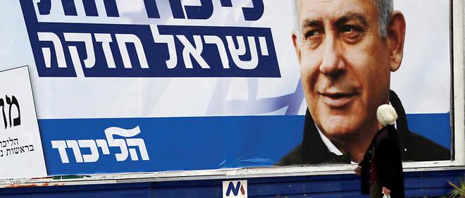 An Israeli Arab woman walks past an electoral billboard showing Israel's Prime Minister Benjamin Netanyahu, in the northern Israeli city of Haifa on April 4, 2019. - Israeli General elections will be held on April 9, 2019. (Photo by AHMAD GHARABLI / AFP)