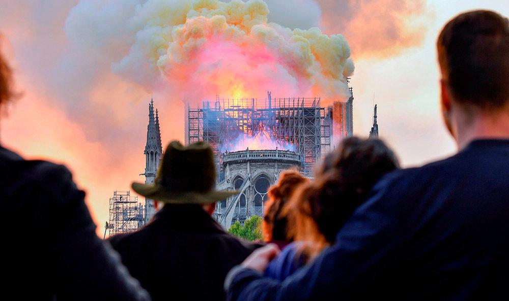 Sidération. Parisiens et touristes, unis dans l'affliction, regardent impuissants le feu dévorer la charpente de Notre-Dame.