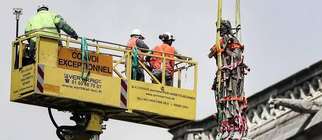 Des ouvriers prennent des mesures de protection pour une statue a Notre-Dame le 29 avril.