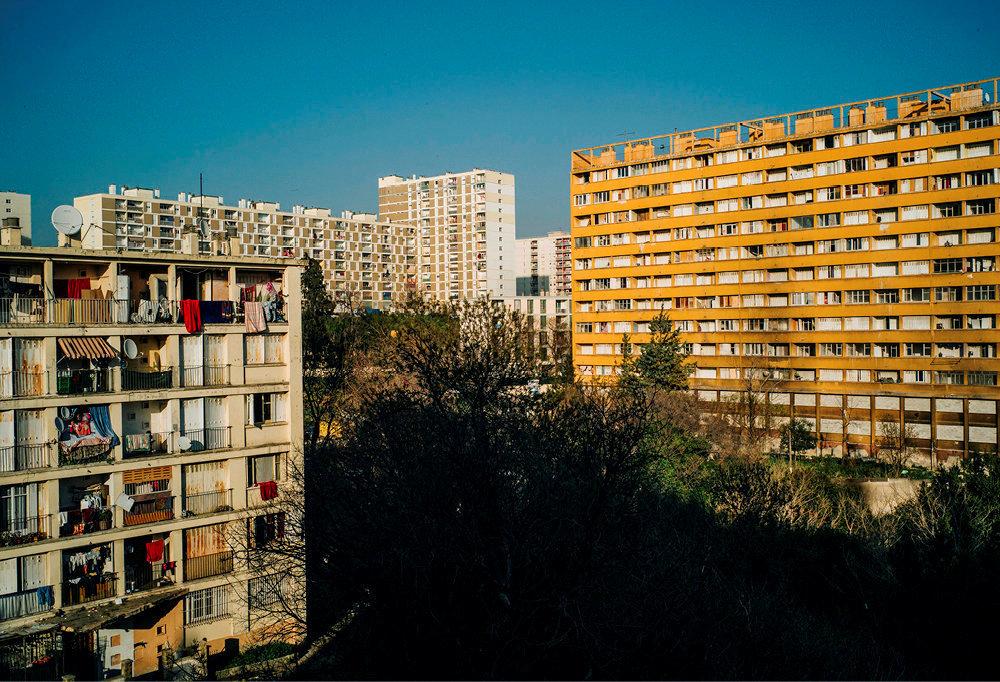 Barres. Un des sept immeubles de la résidence du Parc Corot (à g.) et les cités alentour, à Marseille. L'immeuble de droite, frappé d'insalubrité, a été évacué en décembre 2018.
