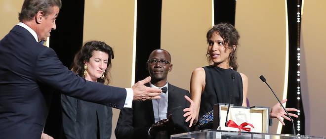La réalisatrice franco-sénégalaise Mati Diop reçoit le Grand Prix du Festival de Cannes des mains de l'acteur américain Sylvester Stallone.