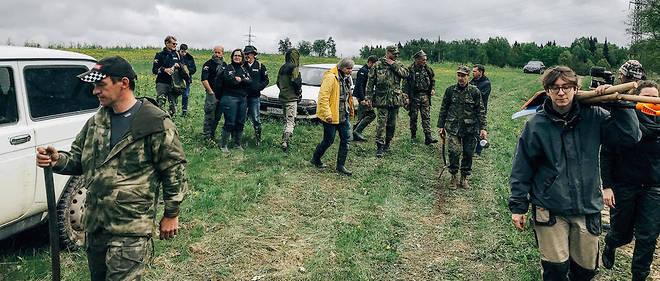 """Les archéologues russes et français, accompagnés d'une association intitulée """"Le Bataillon"""" (les hommes en treillis, à gauche de la photo), marchent en direction du chantier de fouille."""