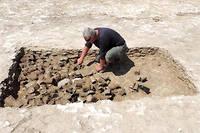 Un archéologue de l'Inrap explore une fosse-dépotoir contenant les restes de rations alimentaires sur le site d'un ancien camp militaire canadien occupé du 25 juillet au 5 août 1944 à Fleury-sur-Orne (Calvados).