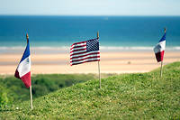 Des drapeaux américains et français flottent au-dessus de la plage d'Omaha Beach.