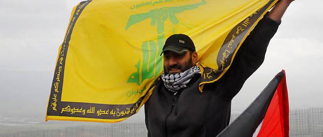 Un manifestant brandit un drapeau du Hezbollah à l'occasion d'un rassemblement organisé par le mouvement islamiste chiite à Adeisseh, à la frontière israélo-libanaise.
