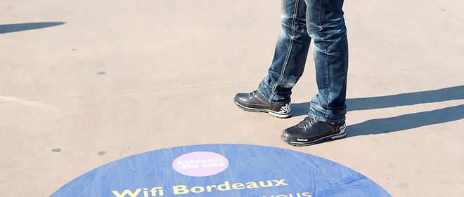 """Le wifi gratuit de la Ville de Bordeaux est desormais actif sur les quais de la ville. Connexion gratuite, marquage au sol """"Wifi Bordeaux, connectez vous gratuitement"""".Ordinateur portable"""