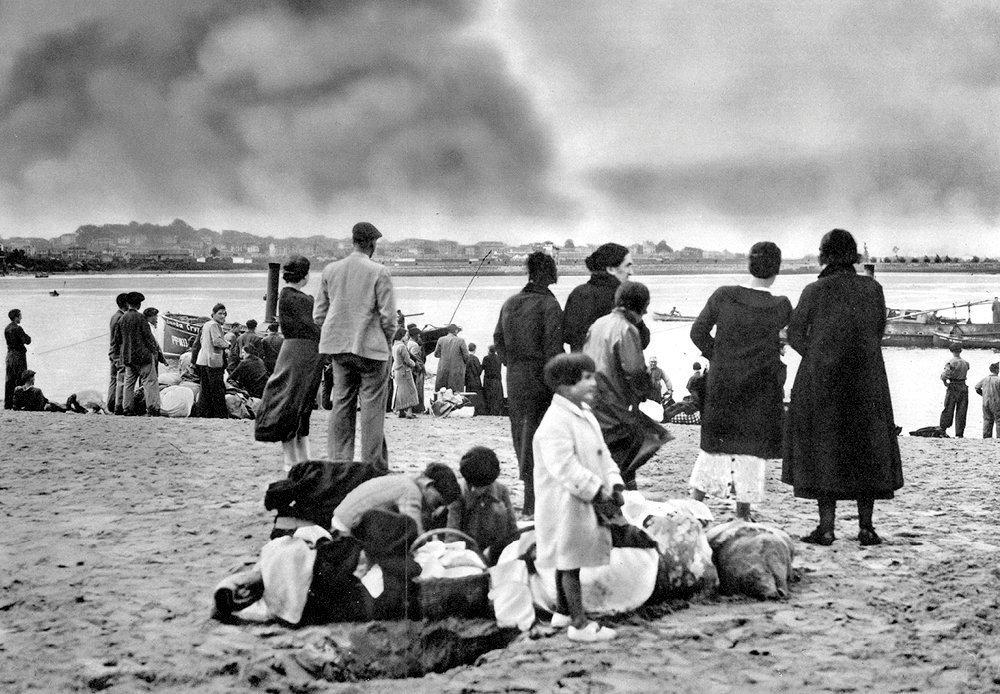 Désarmés. Sur la plage d'Hendaye, en France, des refugiés espagnols venus d'Irun regardent, impuissants, leur ville brûler (1936).
