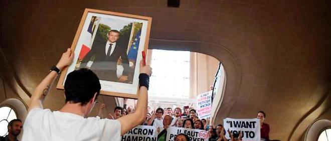 Un homme brandit le portrait d'Emmanuel Macron, décroché à Paris, le 24mai.