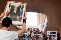 <p>Un homme brandit le portrait d'Emmanuel Macron, décroché à Paris, le 24mai.</p>