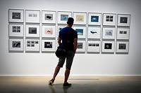 Un homme regarde un mur de photo aux rencontres d'Arles.