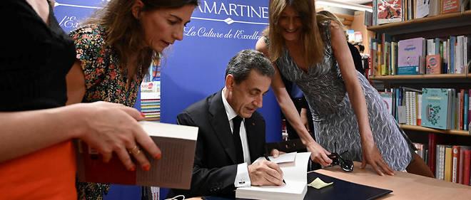 Accompagné de sa femme, Nicolas Sarkozy dédicace son livre dans une librairie de Paris, le 28 juin 2019.