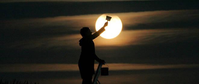 Photographie mise en scène pendant l'éclipse partielle de Lune du 7 septembre 2006 : un peintre semble obscurcir l'astre sélène à mesure qu'il plonge dans l'ombre de la Terre.