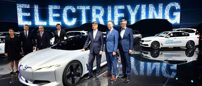 Oliver Zipse (2eme à gauche) remplace Harald Krüger (la main sur la voiture) à la tête de BMW pour accélérer le programme électrique