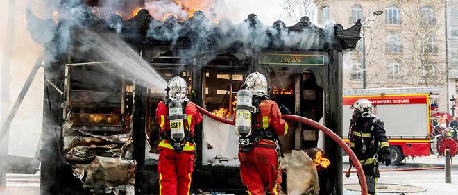 Les pompiers interviennent sur un kiosque à journaux incendié lors de l'acte XVIII des Gilets jaunes à Paris.