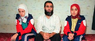 Photo prise le 9 octobre 1989 à Creil (Oise) au domicile de Fatima Achaboun (D) et de sa soeur Leila (G), élèves d'un lycée de Creil qui leur a interdit de porter le tchador en classe. Au centre est assis leur père Ali.